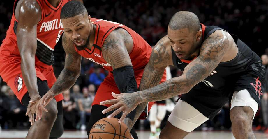 Portland Trail Blazers guard Damian Lillard, left, and Houston Rockets forward P.J. Tucker, right, go after a loose ball during the first half of an NBA basketball game in Portland, Ore., Wednesday, Jan. 29, 2020. (AP Photo/Steve Dykes) Photo: Steve Dykes/Associated Press
