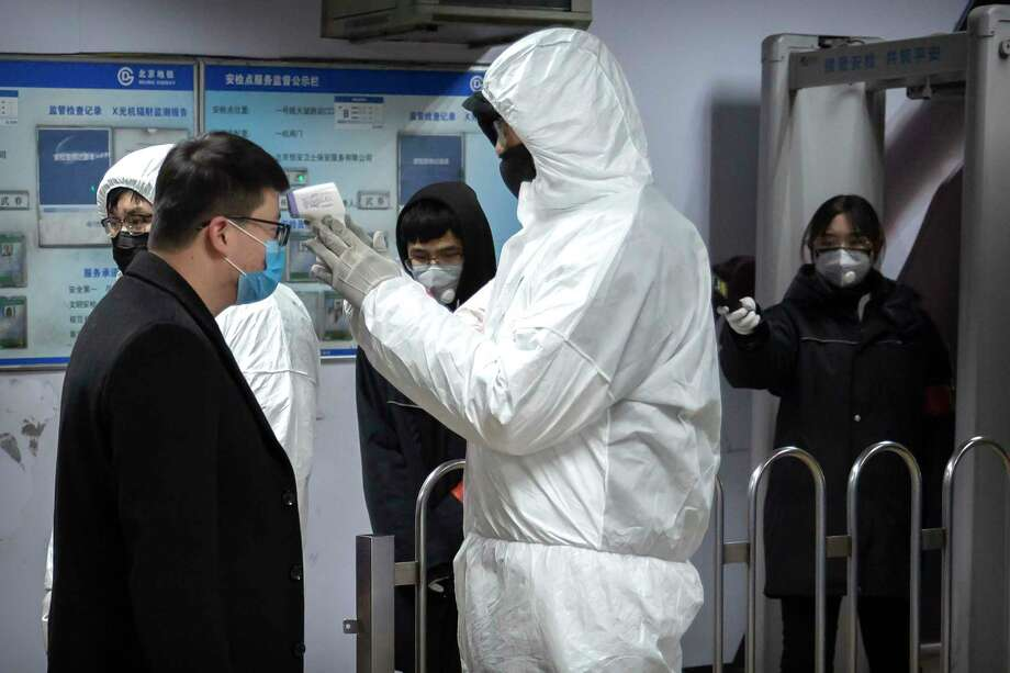 A worker wearing a hazardous materials suit takes the temperature of a passenger at the entrance to a subway station in Beijing, Sunday, Jan. 26, 2020. (AP Photo/Mark Schiefelbein) / Copyright 2020 The Associated Press. All rights reserved