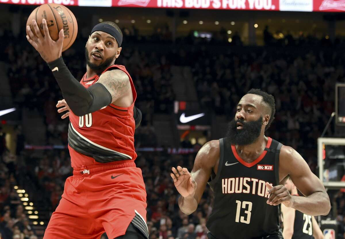 Portland Trail Blazers forward Carmelo Anthony, left, catches the ball in front of Houston Rockets guard James Harden during the second half of an NBA basketball game in Portland, Ore., Wednesday, Jan. 29, 2020. The Blazers won 125-112. (AP Photo/Steve Dykes)