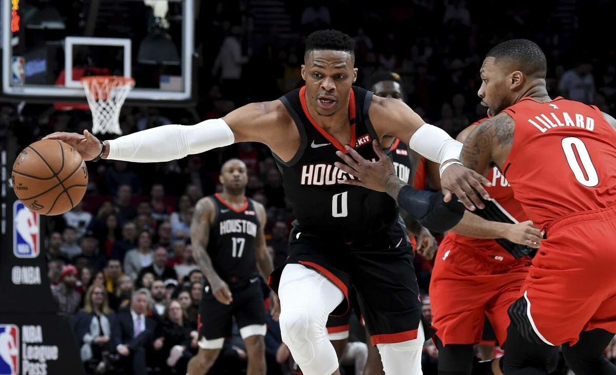 Houston Rockets guard Russell Westbrook, left, dribbles the ball next to Portland Trail Blazers guard Damian Lillard, right, during the first half of an NBA basketball game in Portland, Ore., Wednesday, Jan. 29, 2020. (AP Photo/Steve Dykes)