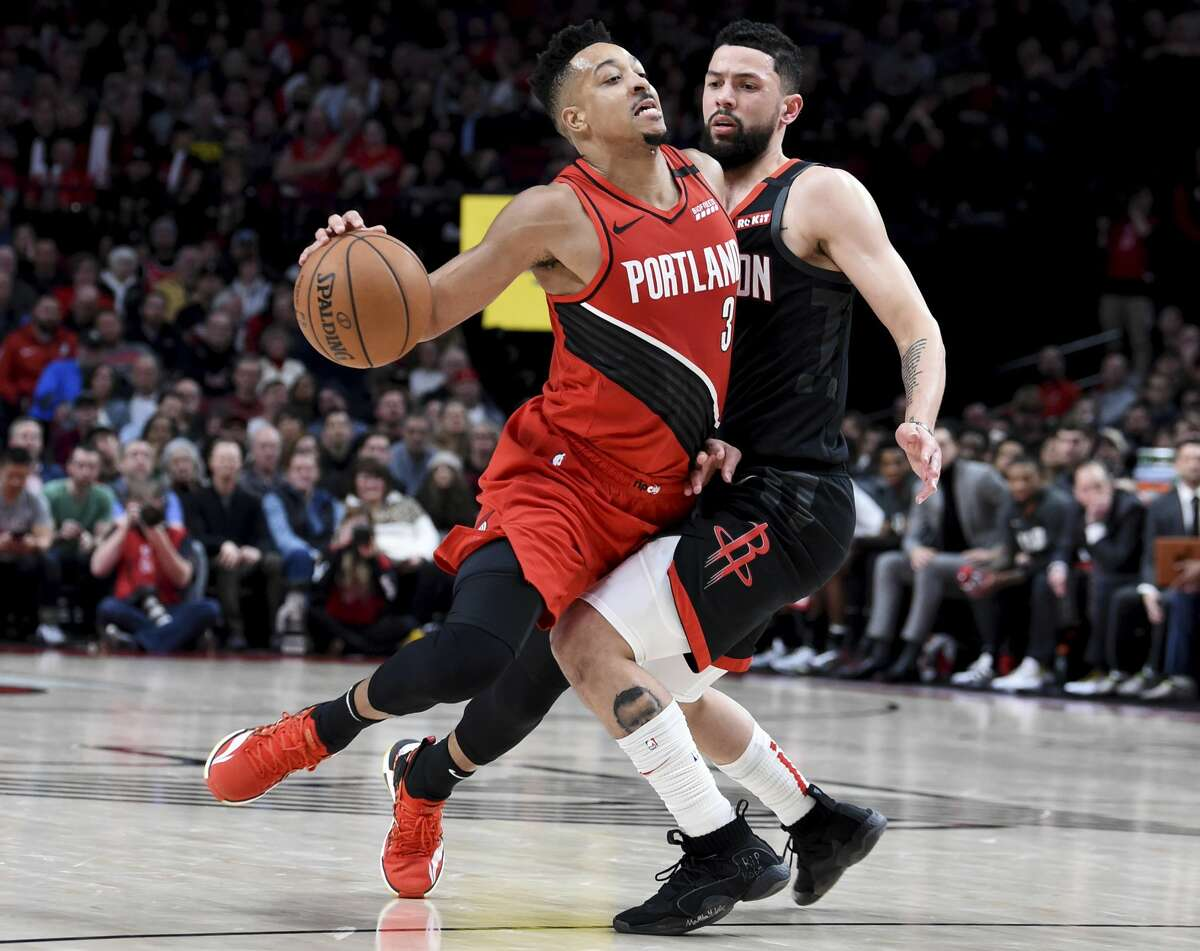 Portland Trail Blazers guard CJ McCollum, left, is fouled by Houston Rockets guard Austin Rivers on a drive to the basket during the second half of an NBA basketball game in Portland, Ore., Wednesday, Jan. 29, 2020. The Blazers won 125-112. (AP Photo/Steve Dykes)