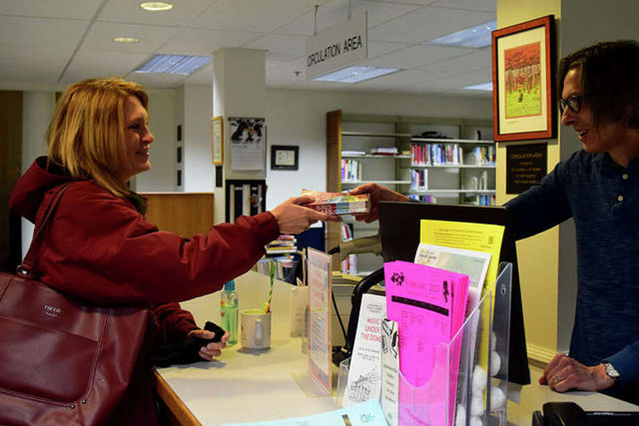 Tami Balthis of Jacksonville checks out a library book from librarian Andy Mitchell at Jacksonville Public Library.