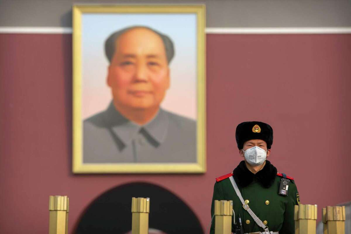 A policeman wears a face mask as he stands guard near the large portrait of Chinese leader Mao Zedong in Tiananmen Square in Beijing.