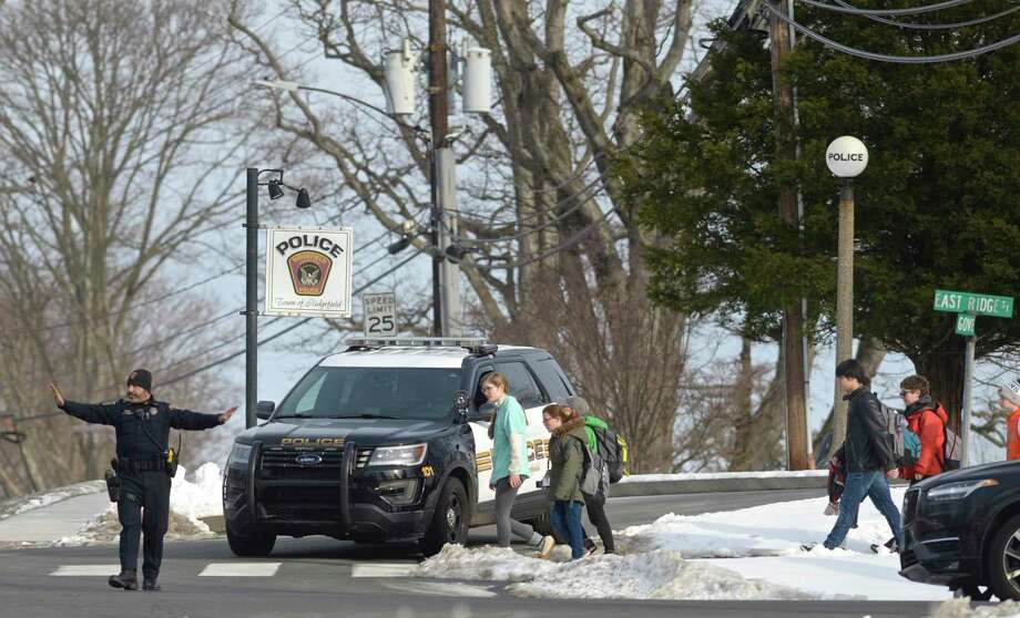 A Ridgefield police officer mans a crosswalk to allow students from East Ridge Middle School to cross in front of the town police station. Thursday, January 23, 2020, in Ridgefield, Conn. Photo: H John Voorhees III / Hearst Connecticut Media / The News-Times