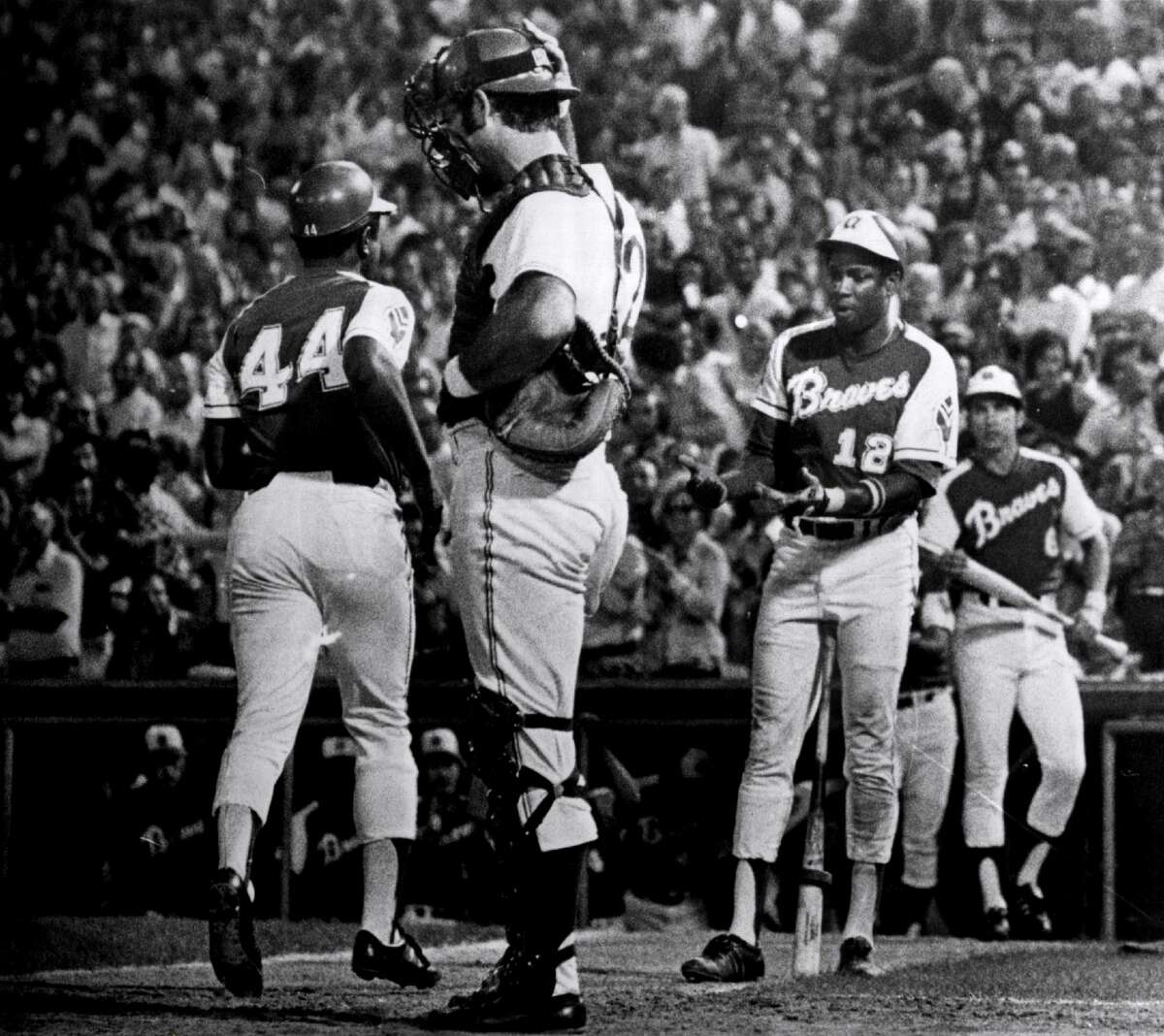 Dusty Baker of the Atlanta Braves congratulates teammate Hank Aaron after Aaron's 703rd home run on Aug. 17, 1973. (Photo by Sporting News via Getty Images via Getty Images)