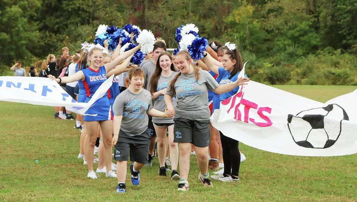 Members of last year's Regional School District 13 Durham/Middlefield Unified Sports team break through a banner held by cheerleaders.