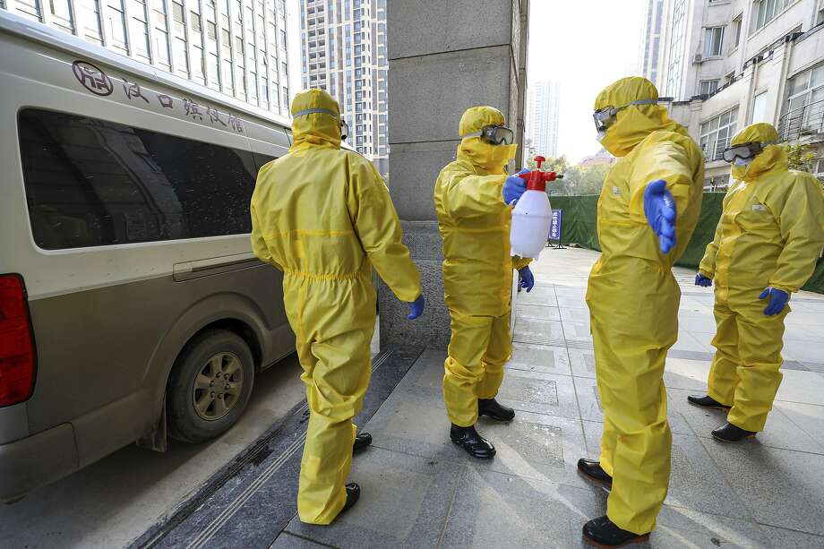 Funeral workers disinfect themselves after handling a virus victim in Wuhan, the Chinese city at the epicenter of the virus outbreak. Photo: Associated Press