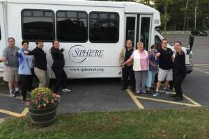 The SPHERE bus and its organizers. The town purchased the bus from the organization, and is considering using it to transport workers to town from the Branchville train station.