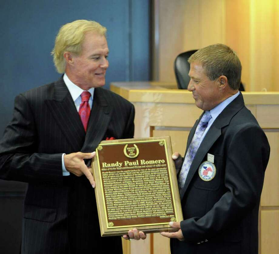 Jockey Randy Romero, left, receives a plaque from C. Kenneth Dunn to mark Romero's induction into the National Thoroughbred Racing Hall of Fame. (Skip Dickstein/Times Union) Photo: Skip Dickstein