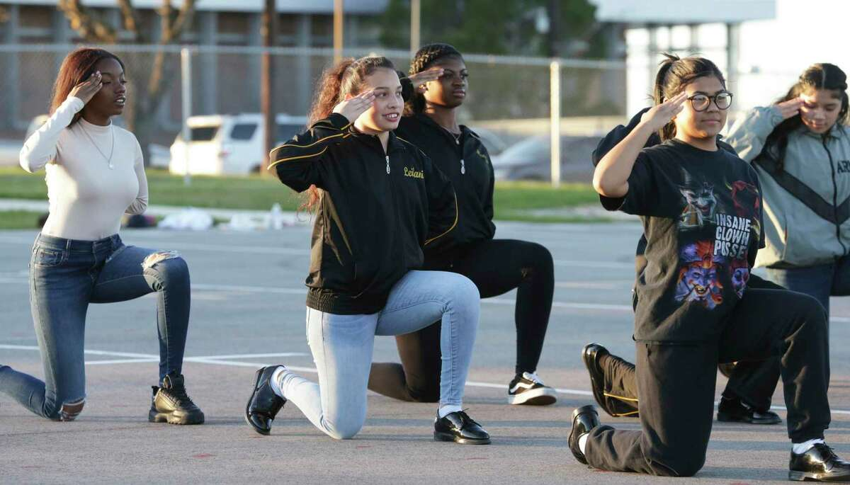 Jenevie Sacriste, center, enjoys the moment as the East Central High School unarmed drill team practices for the Army JROTC National Drill Championship in March.