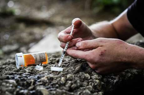 A man prepares a shot of heroin and cocaine. More than 400,000 people have died in the nation's opioid crisis in the past two decades. MUST CREDIT: Washington Post photo by Salwan Georges