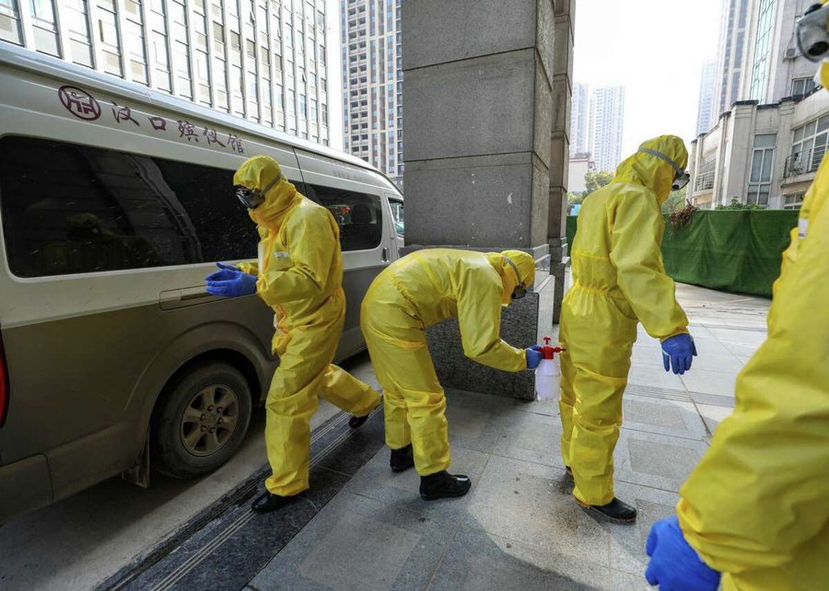 Workers from a funeral home disinfect themselves after handling a coronavirus victim in a hospital in Wuhan, China.