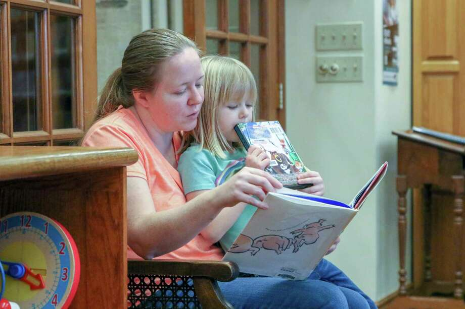 Kellee Roth of Bad Axe reads to her daughter, Everlee, 4, as her son Wilder (not pictured) plays at the Bad Axe District Library recently. (Eric Young/Huron Daily Tribune) / © Huron Daily Tribune 2019