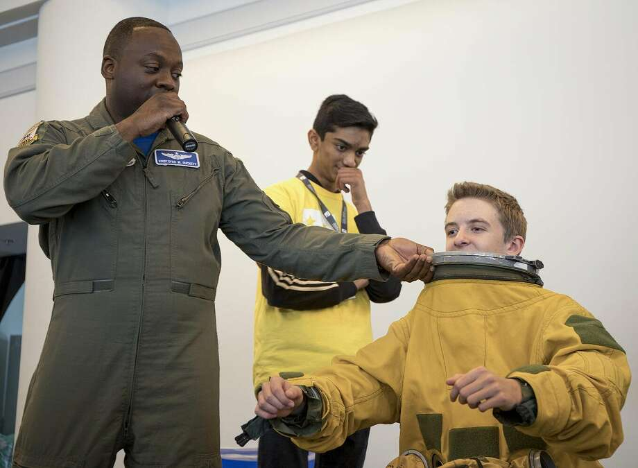 U.S. Air Force U-2 pilot shows MPA Day student how to wear his Air Force flight suit. Photo: Ted Huetter/The Museum Of Flight