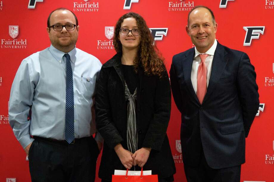 Isabella Silva, who won third place in the Martin Luther King Jr. essay contest, is pictured with Matthew Schirano of Fairfield University, left, and Fairfield University President Mark R. Nemec. Photo: Contributed Photo