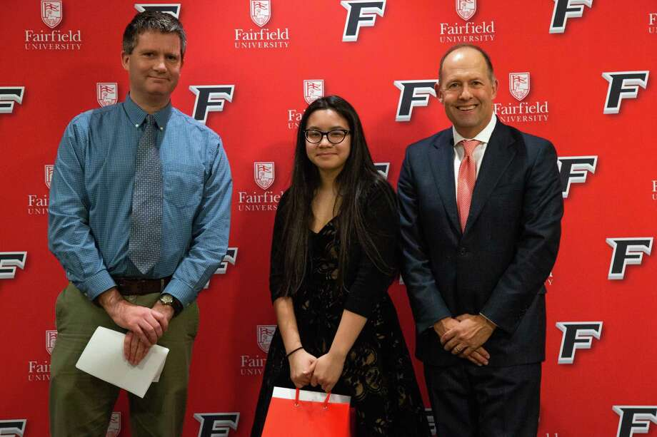 Julia Alcantara, who won second place in this year's Martin Luther King essay contest, is pictured with Hugh Bailey, Connecticut Post, and Fairfield University President Mark R. Nemec. Photo: Contributed Photo