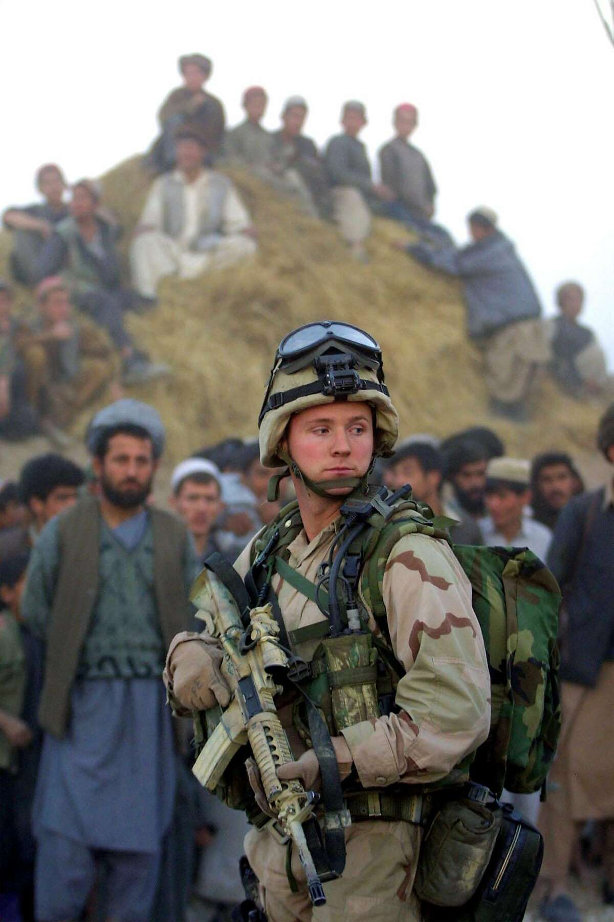FILE - In this Nov. 15, 2001 file photo, at sundown, a U.S. Army Special Forces soldier stands guard near a helicopter, not pictured, as Afghan civilians and militia members loyal to the northern alliance look on, in Khwaja Bahuaddin, Afghanistan, 350 kilometers (220 miles) northeast of Kabul. For 10 years, ever since the towers fell, the United States has fought a war in a distant land _ in hopes, it says, of protecting American interests and making the world safer from terrorism. Now, as President Barack Obama plans to end U.S. combat operations in Afghanistan by 2014, the question remains as muddy as ever: What happened here? (AP Photo/Brennan Linsley, File)