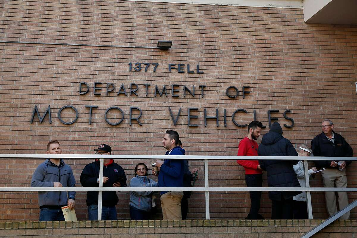 People are seen lined up in a driver's license non-appointment line outside the DMV on Fell Street on Friday, January 24, 2020 in San Francisco, Calif.