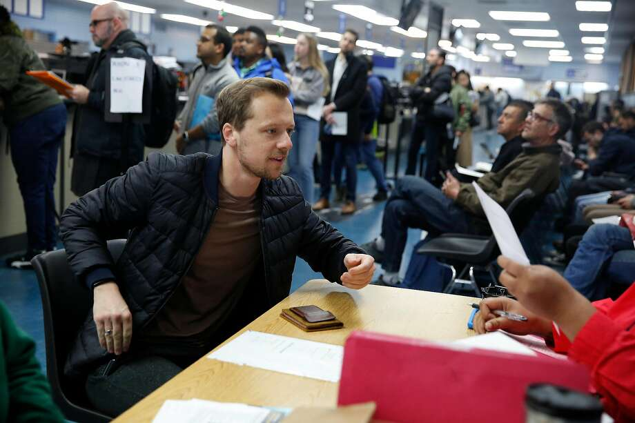 Julian Riediger, left, of San Francisco is helped by DMV technician Renita Head at a table for Real ID Express appointments while those without appointments wait in line at the DMV office on Fell Street on Friday, Jan. 24, 2020 in San Francisco, Calif. Many services at the DMV have changed since the coronavirus outbreak, and in-office visits are now by appointment only. Photo: Lea Suzuki / The Chronicle
