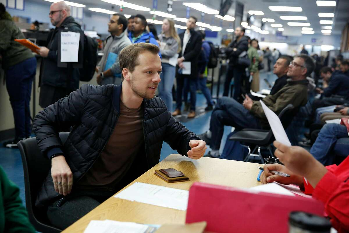 Julian Riediger (l to r) of San Francisco is helped by Renita Head, DMV technician, at a table for Real ID Express appointments while those without appointments wait in line behind him at the DMV on Fell Street on Friday, January 24, 2020 in San Francisco, Calif.