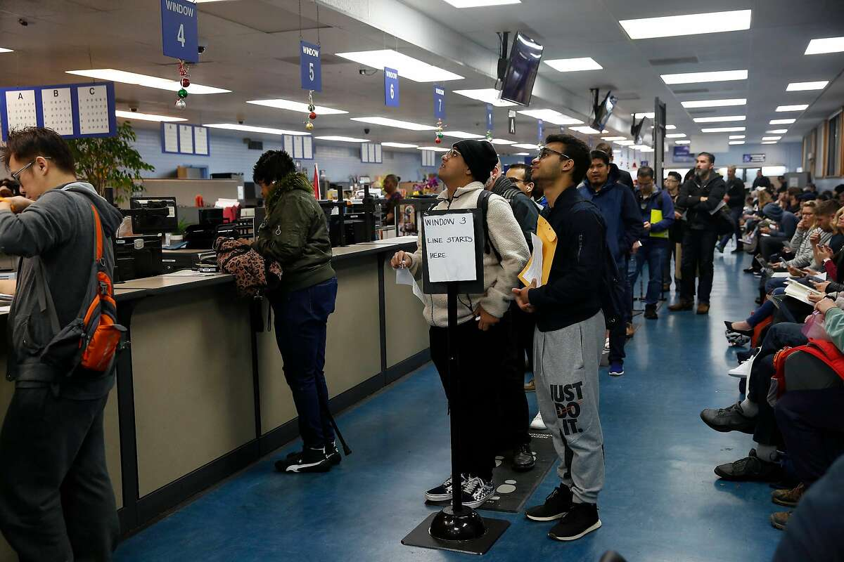 Elias Dubaie ( center l to r) of San Francisco and Kahlai Pratt of San Francisco watch a sign board while they wait in line to apply for the Real ID at the DMV on Fell Street on Friday, January 24, 2020 in San Francisco, Calif.