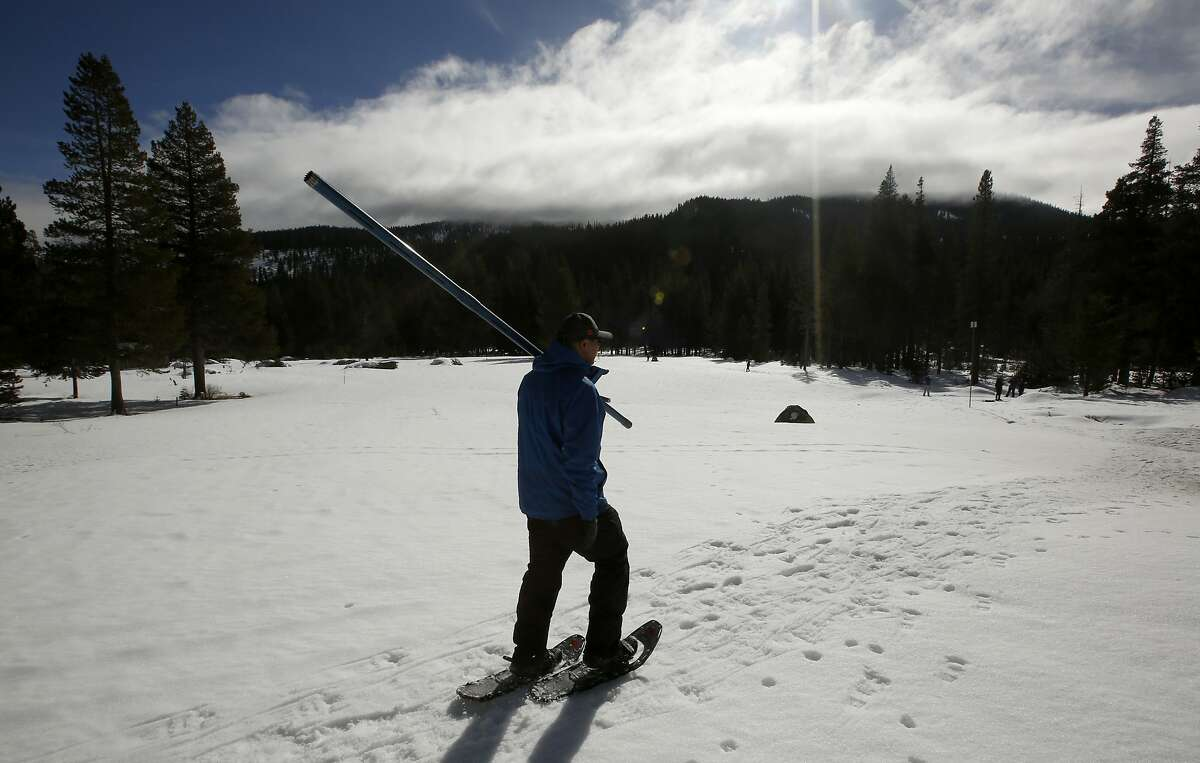Sean de Guzman, chief of snow surveys for the California Department of Water Resources, carries the snow survey tube as he walks across a snow covered field during the second snow survey of the season at Phillips Station near Echo Summit , Calif., Thursday, Jan. 30, 2020. The survey found the snowpack at 40. 5 inches deep with a water content of 14.5 inches.