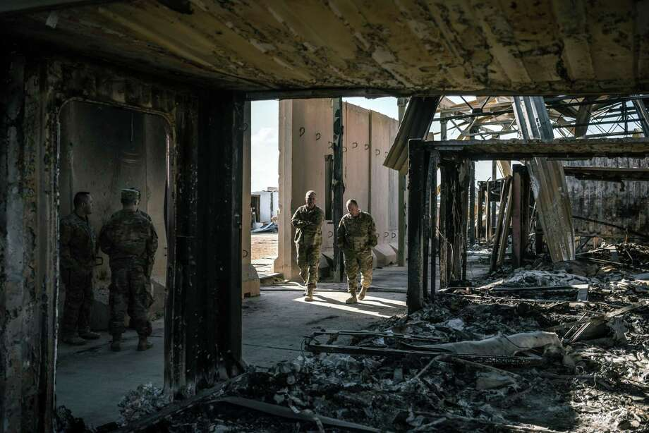 """U.S. military personnel survey the damage to a building that was struck by Iranian missiles at Al Asad Air Base in Anbar, Iraq, Jan. 13. Trump, on Jan. 22, dismissed concussion symptoms reported by several American troops after Iranian airstrikes on Al Asad Air Base as """"not very serious."""" Photo: SERGEY PONOMAREV /NYT / NYTNS"""