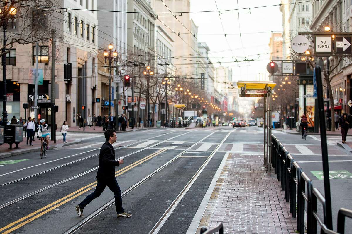 A man walks across an empty Market Street in San Francisco, Calif. Wednesday, January 29, 2020. Beginning January 29, private vehicles will be banned from driving along Market Street between Steuart and 10th streets, leaving it free for cyclists, pedestrians and public transit vehicles.