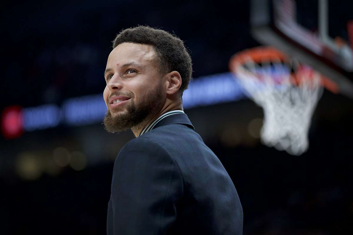 Golden State Warriors guard Stephen Curry smiles from the bench during the second half of an NBA basketball game against the Portland Trail Blazers in Portland, Ore., Monday, Jan. 20, 2020. The Trail Blazers won 129-124 in overtime. (AP Photo/Craig Mitchelldyer)