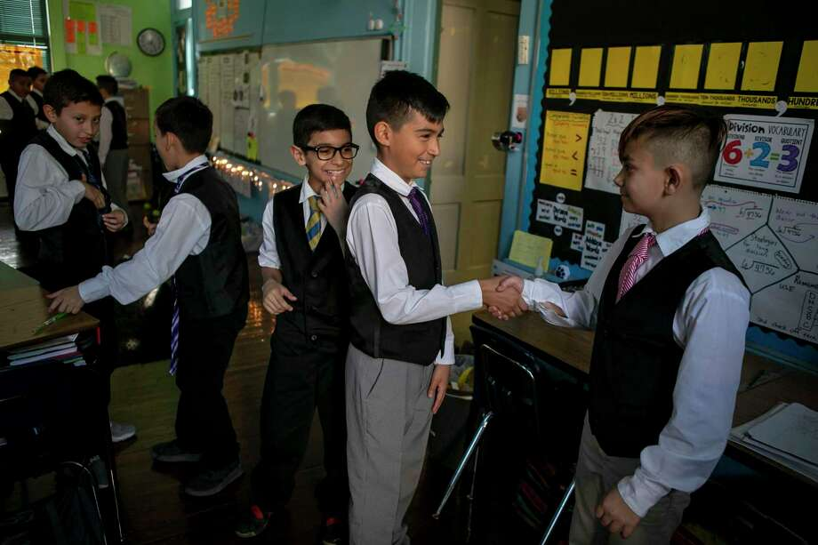 Sonny Aguirre, 10, shakes the hand of his friend Abner Pulido, 10, before an after-school meeting of Caballeros Distinguidos, a boys-only etiquette club, at Briscoe Elementary School. A reader is proud of the young gentlemen. Photo: Josie Norris / Staff Photographer / **MANDATORY CREDIT FOR PHOTOG AND SAN ANTONIO EXPRESS-NEWS/NO SALES/MAGS OUT/TV
