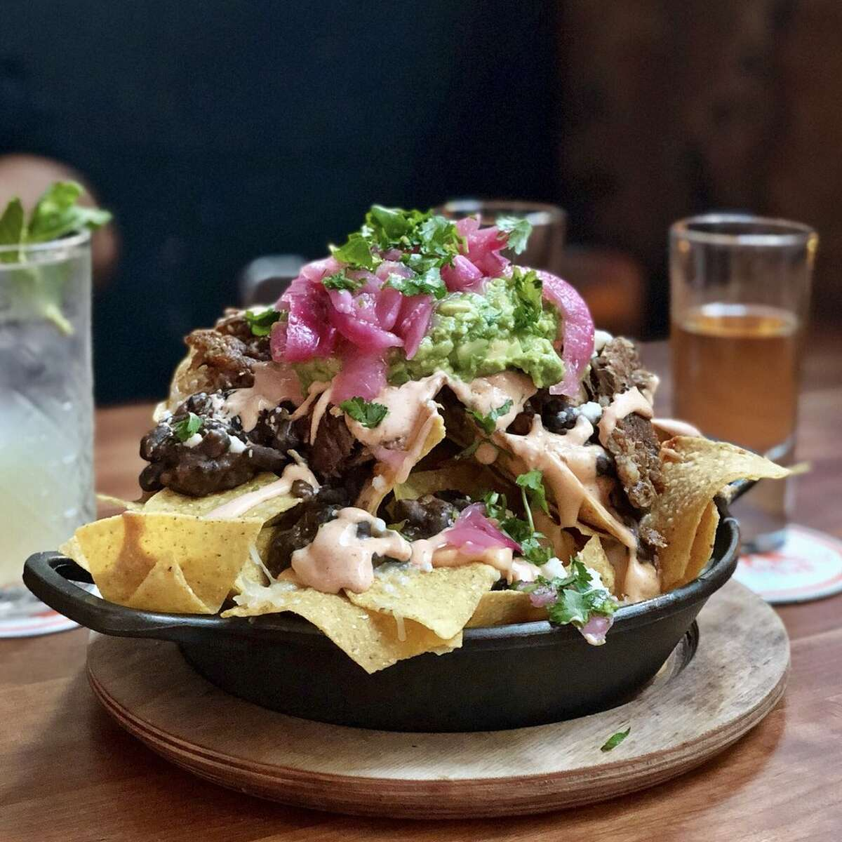 For a hefty tower of nachos, swing by Cantina LenaTom Douglas' Belltown eatery doling out Mexican fare is here for all the nacho fixings. Pull tortilla chips from gargantuan plates of cantina nachos like a game of Jenga, drenched in toppings like crispy pork carnitas, green chiles with guac, tapatio sour cream, and pickled onion. Or for some vegan grub, nab their nachos coated with cashew-squash cheese, house-made tofu chorizo, escabeche, and cashew sour cream.