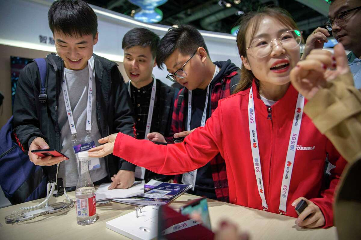 """In this Oct. 31, 2019 photo, an exhibitor talks about Huawei smartphones at a Huawei booth at the PT Expo technology conference in Beijing. Chinese tech giant Huawei is racing to develop replacements for Google apps. U.S. sanctions imposed on security grounds block Huawei from using YouTube and other popular Google """"core apps."""" (AP Photo/Mark Schiefelbein)"""