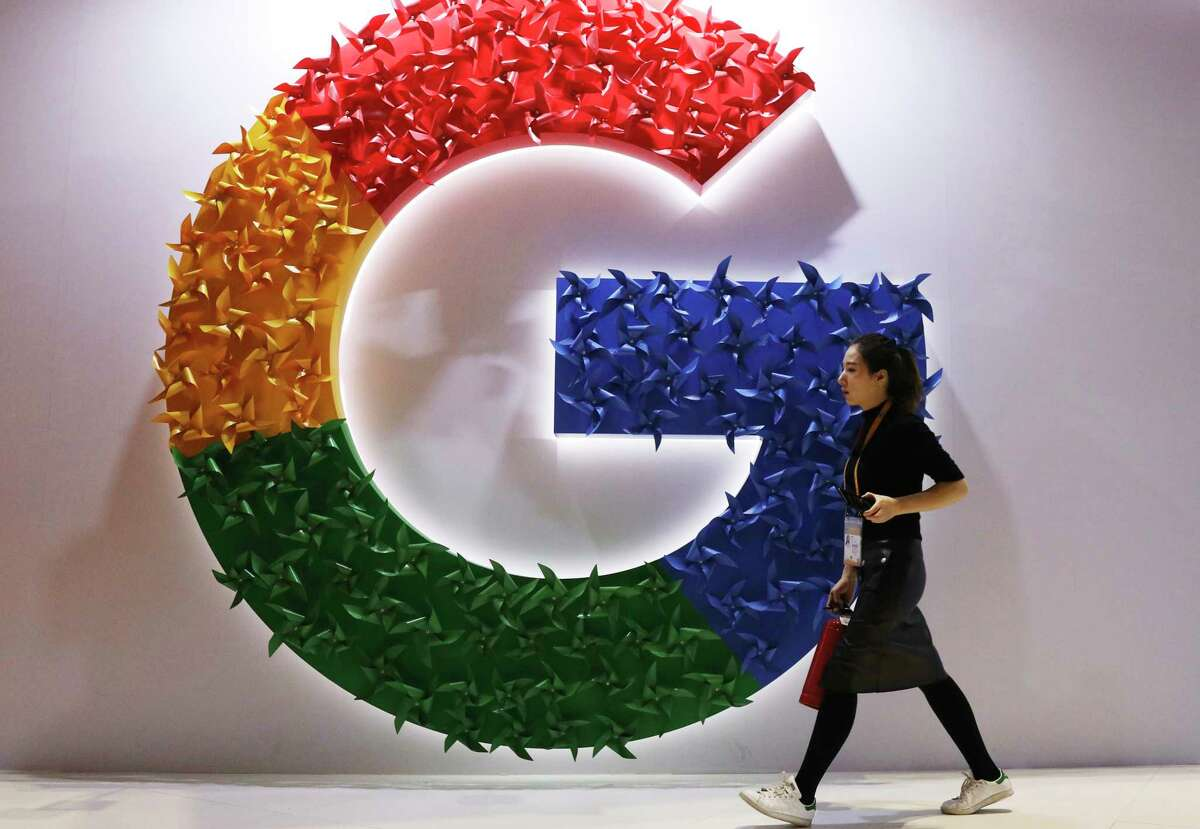 """FILE - In this Monday, Nov. 5, 2018, file photo, a woman walks past the logo for Google at the China International Import Expo in Shanghai. Chinese tech giant Huawei is racing to develop replacements for Google apps. U.S. sanctions imposed on security grounds block Huawei from using YouTube and other popular Google """"core apps."""" (AP Photo/Ng Han Guan, File)"""