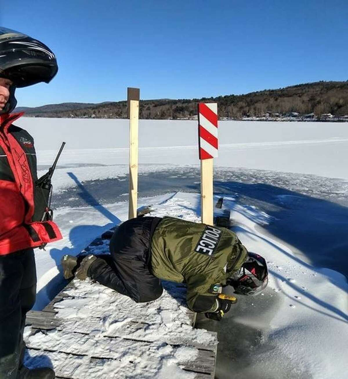 Rangers and ECOs deal with docks frozen in the ice of the Great Sacandaga Lake since the loose docks could be hazards to snowmobilers.
