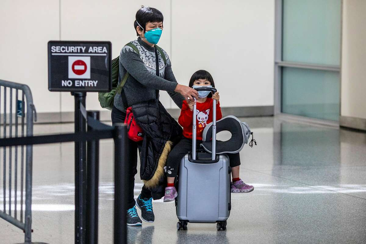 Passengers exit customs at San Francisco Airport's international terminal on Thursday January 30, 2020 in San Francisco, Calif. Airlines are cancelling some flights to China because of concerns over the coronavirus.
