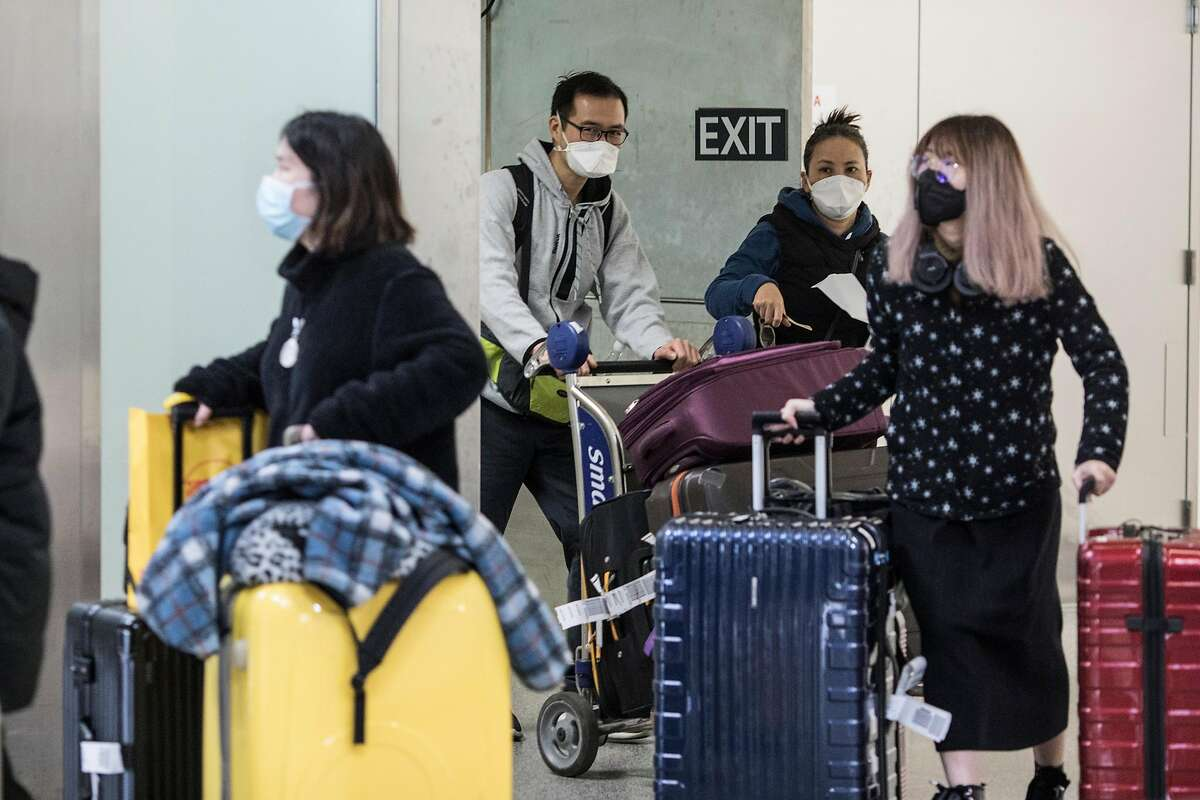Passengers exit customs at San Francisco Airport's international terminal on January 30, 2020 in San Francisco, Calif. Airlines are cancelling some flights to China because of concerns over the coronavirus.