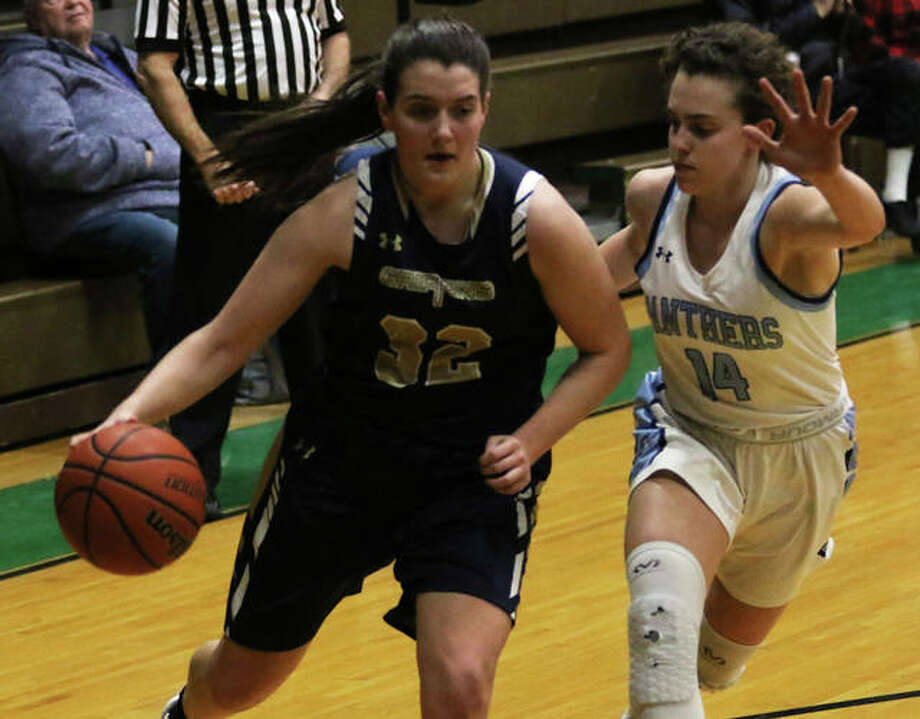 Father McGivney's Madison Webb (left) drives on Jersey's Chloe White in the first half on Thursday night in the semifinals of the Carrollton Tournament.