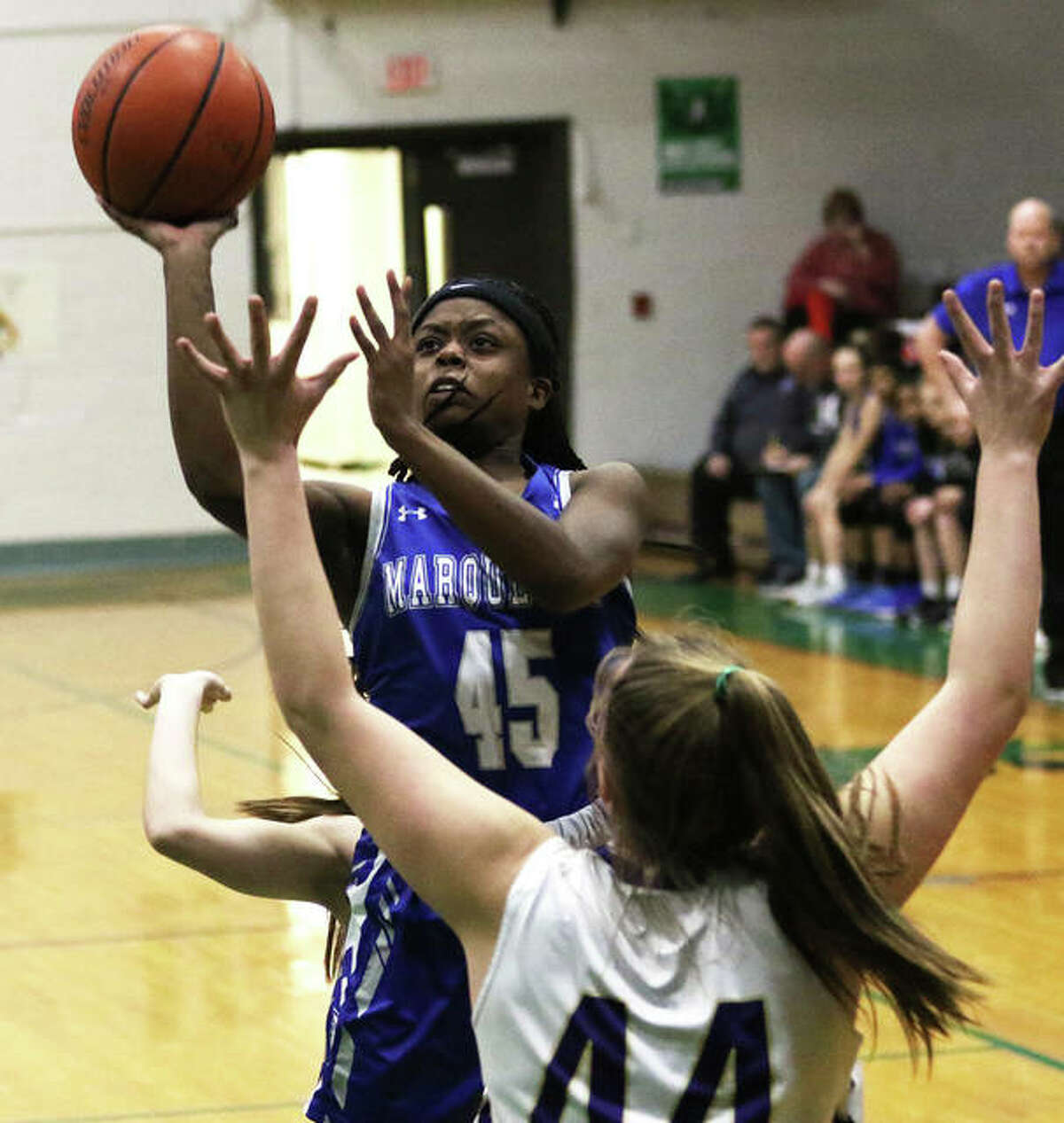 Marquette Catholic's Adrenna Snipes puts up a shot in the lane over Jacksonville Routt's Bella McCartney (44) in the first quarter Thursday night in the semifinals of the Carrollton Tourney.