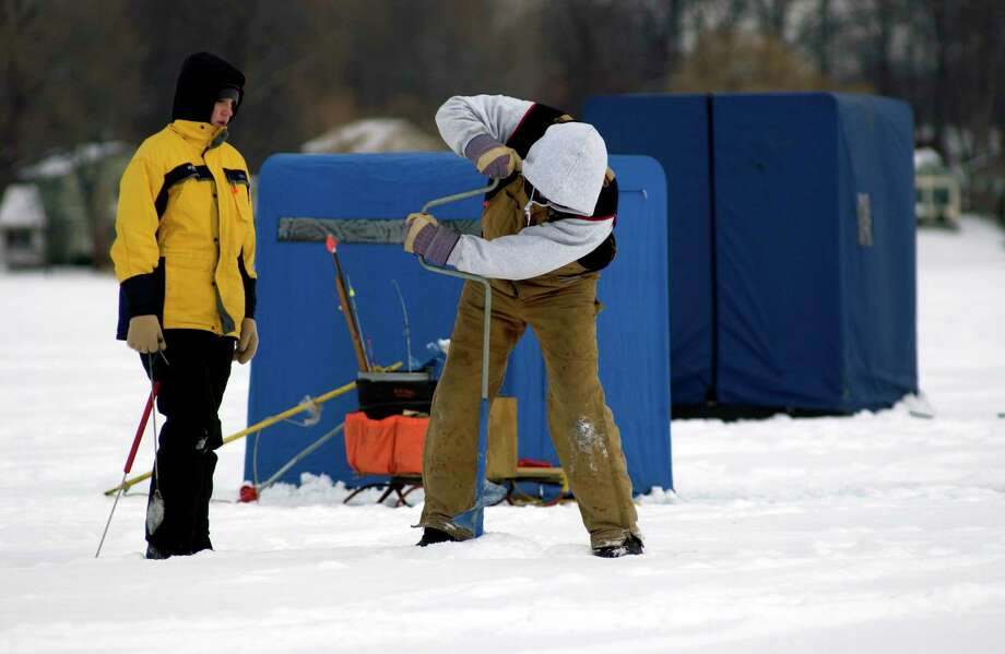 An ice fisherman plunges a hole in the ice using a hand-crank auger. (Michigan DNR/Courtesy Photo) / Copyright 2003 State of Michigan
