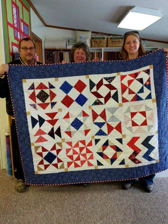 Picucci and another QOVF member present a quilt to a local veteran at a previous quilting event. They are hoping to gift a veteran with one of their quilts Saturday as well. (Courtesy photo)