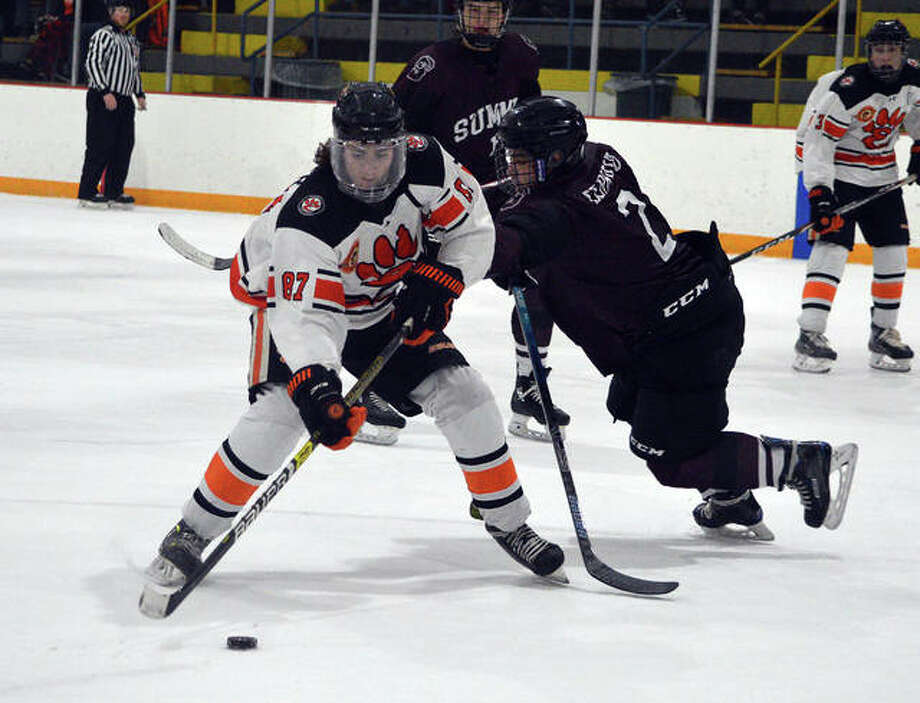 Edwardsville's Collin Salter, left, battles for the puck with a Rockwood Summit player during Thursday's Mid-States round-robin playoff game at East Alton Ice Arena. Photo: Scott Marion/The Intelligencer
