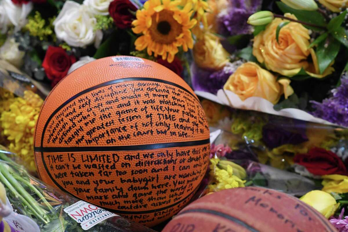 A note written on a basketball is seen among flowers at a makeshift memorial as fans mourn the death of NBA legend Kobe Bryant, who was killed along with his daughter and seven others in a helicopter crash on January 26, at LA Live plaza in front of Staples Center in Los Angeles on January 27, 2020.
