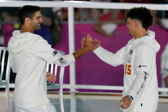 Kansas City Chiefs' Patrick Mahomes, right, greets San Francisco 49ers' Jimmy Garoppolo during Opening Night for the NFL Super Bowl 54 football game Monday, Jan. 27, 2020, at Marlins Park in Miami. (AP Photo/Morry Gash)
