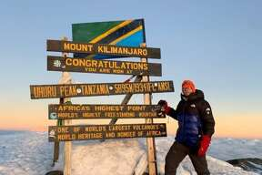 Manistee native Dominic Peterson poses at Uhuru Peak on Mt. Kilimanjaro during his climb to the peak. Peterson joined 23 others in climbing the mountain to help raise awareness and funds for the fight against Alzheimer's Disease.