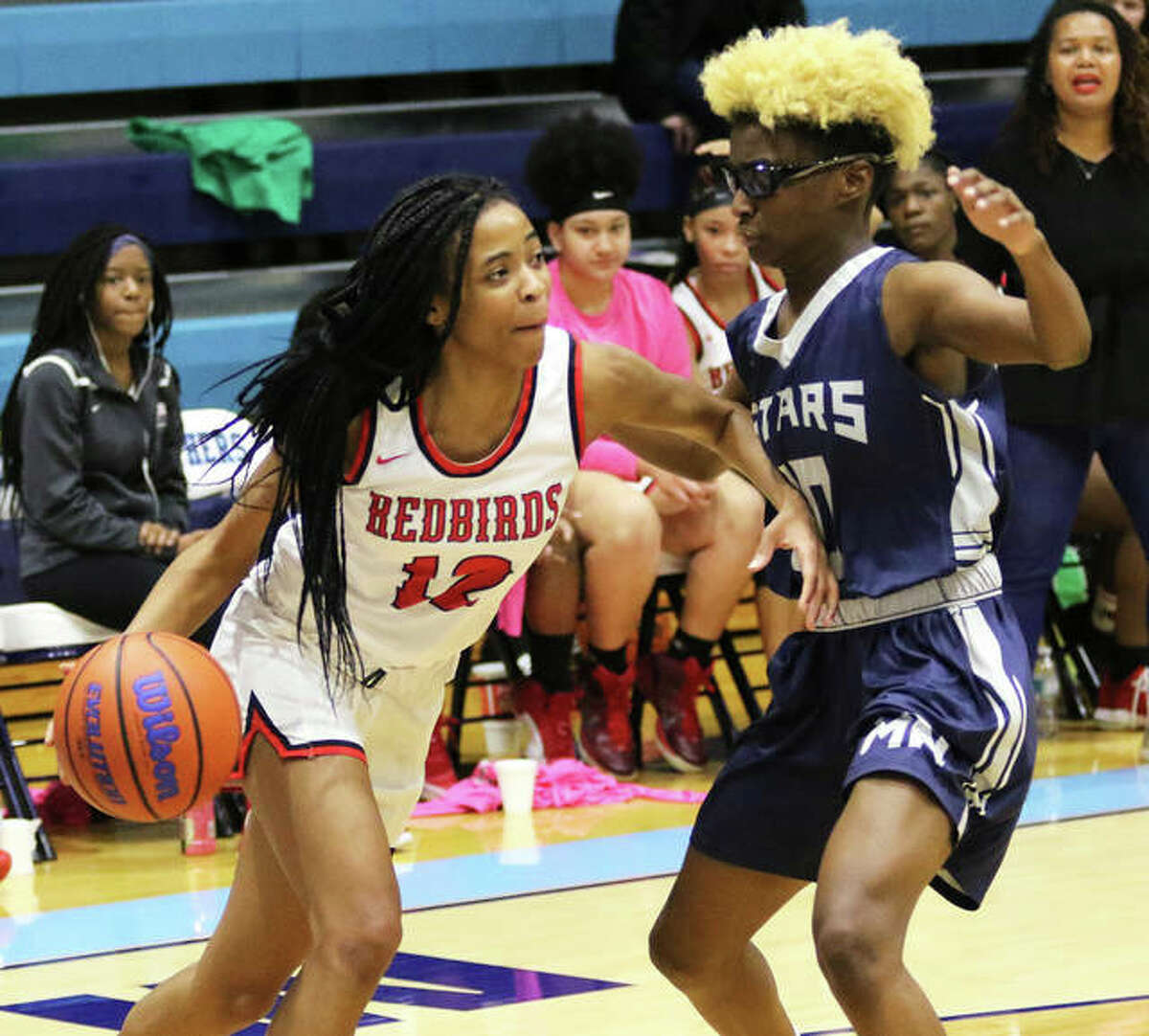 Alton's Germayia Wallace (left) drives on a McCluer North defender in a Jersey Tourney game Dec. 27 in Jerseyville. Alton ended an 11-game losing streak Thursday night with a victory at the Hillsboro (Mo.) Tourney.