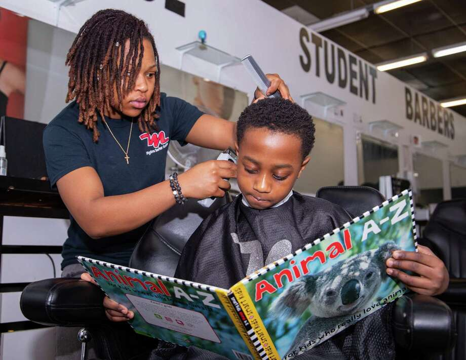 Young clients at Mystros Barber Academy enjoy reading while getting their hair cut. Children can select books from a waiting room library as part of the Books in the Barbershop Literacy Program--a community partnership with Spring ISD. Photo: Courtesy Of Spring ISD / SPRING ISD SPRING ISD