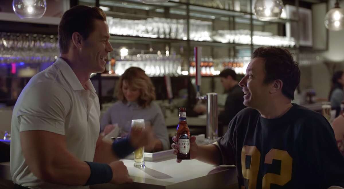 This undated image provided by Michelob ULTRA shows John Cena, left, and Jimmy Fallon in a scene from the company's 2020 Super Bowl NFL football spot. Michelob Ultra stresses its low calories and low carbs in an ad that shows talk show host Jimmy Fallon and wrestler John Cena working out. (Michelob ULTRA via AP)