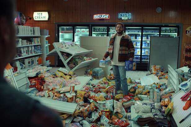 This undated image provided by Bud Light shows Post Malone in a scene from the company's 2020 Super Bowl NFL football spot. Anheuser-Busch is having fans choose between two ads that feature singer Post Malone sipping a fruity new Bud Light Seltzer. (Bud Light via AP)