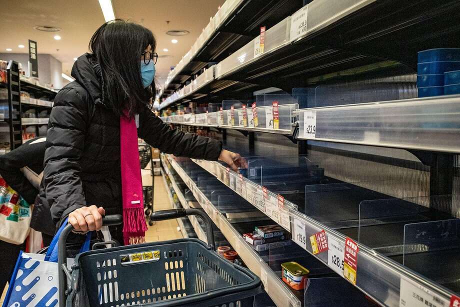 A customer wears a face mask to protect against the new virus while shopping at a grocery store in Hong Kong. Photo: Anthony Kwan / Getty Images