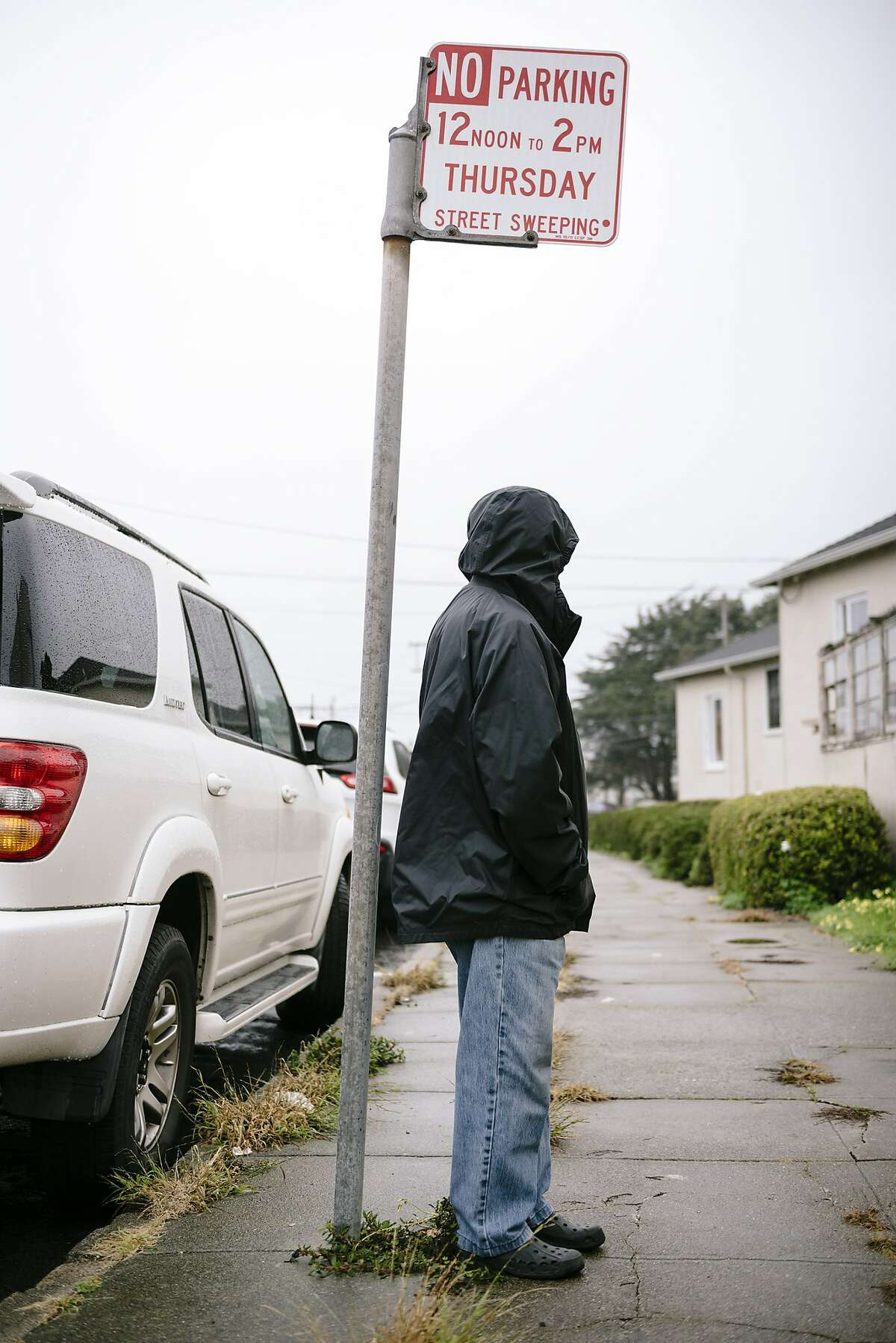 Anthony De Guzman stands for a portrait under a street sweeping sign near where left his car parked and received a ticket while he was in the hospital for two weeks after being robbed and stabbed on the steps of his home in San Francisco, Calif, on Tuesday, January 28, 2020.